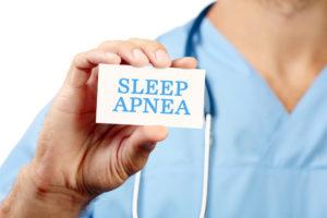 Doctor holding card with text SLEEP APNEA, closeup